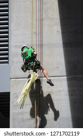 Industrial abseiler, abseiling down the side of a concrete structure