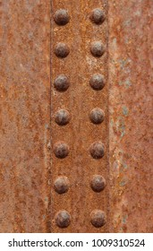 Industrial abstract textured vertical pattern. Vertical row of rusted rivets selective focus