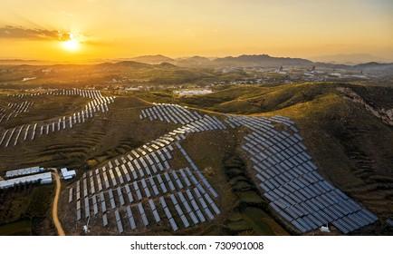 Industrial aerial sunrise mountain solar photovoltaic power plant