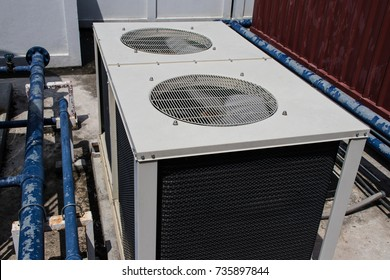 Industrial air conditioning compressor units installed outdoor on rooftop of the building with blue pipeline