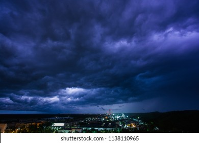 Industrial area on a background of thunderstorm and lightning. Beautiful dramatic sky illuminated by lightning above paper mill and thermal power station at night. A combination of industry and nature