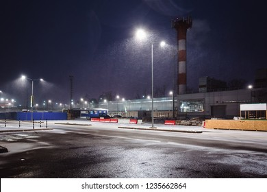 Industrial area on the outskirts of the city at night. Street lights illuminate the snow falling from above.