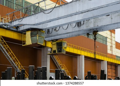 Industrial area. Outdoors crane trestle. Overhead traveling crane above the open warehouse and loading area.
