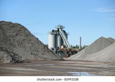 An industrial asphalt plant surrounded by piles of gravel.