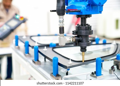 Industrial automated robot arm holding car glass in factory