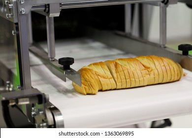 Industrial automatic bread slicer machine for bakeries. Selective focus.