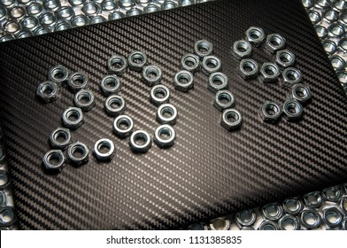 Industrial background for Christmas and New Year's calendar. 2019 text from hex  metal nuts on carbon texture.