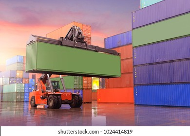 Industrial background of container depot and reach stacker is working to carry green container during sunset beautiful sky.