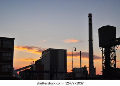 Industrial background with factory buildings on red sky