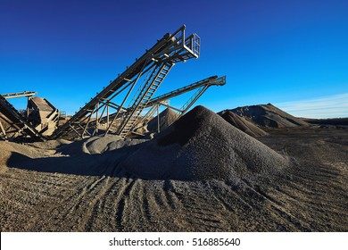 Industrial background with gravel crusher. Extraction of gravel. Conveyor for transporting gravel. Morning. Beautiful light.