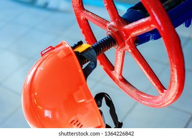 Industrial background. Helmet gas industry worker and a red valve to shut off the pressure in the pipe.