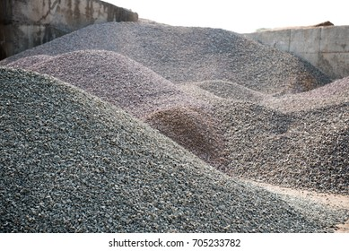 Industrial background with pile of gravel. Extraction of gravel. Construction of roads. Piles of gravel on construction site.