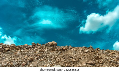 Industrial background with pile of gravel in front of the sky. Extraction of gravel. Construction of roads. Piles of gravel on construction site