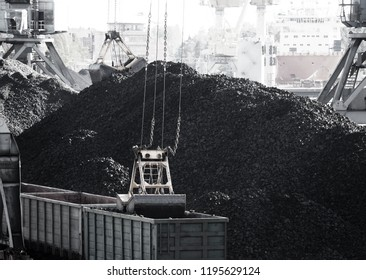 Industrial background. Seaport. Сargo port, loading coal into railway freight wagons, railroad. Cargo terminal, cranes. Black and white monochrome image