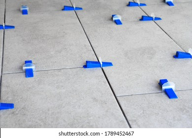 Industrial background. Tile leveling system with plastic clips and wedges,
