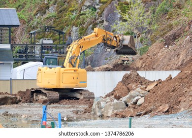 An industrial backhoe is busy moving topsoil in a construction zone for residential housing.