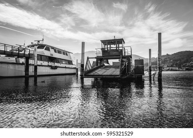 Industrial barge and an old white ferry on the Como lake. Italy, near Milan