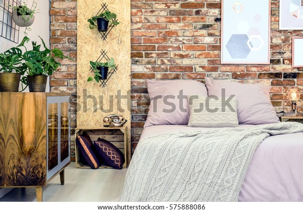 Industrial bedroom with double bed and dirty pink bedding