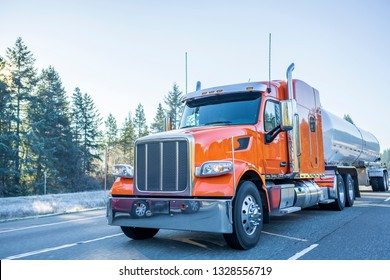 Industrial Big rig low cab bonnet orange classic popular American semi truck transporting commercial liquid cargo and fuel in tank semi trailer moving on the winter frosty road with frost trees