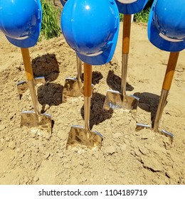 industrial blue hard hats on shovels in dirt for ground breaking ceremony