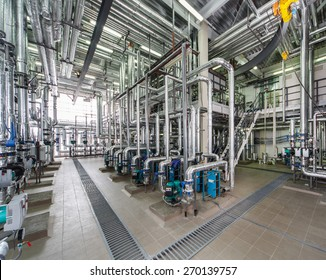 industrial boiler interior with lots of pipes, pumps and valves.