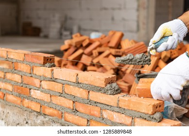 Industrial bricklayer installing bricks on construction site. Detail of hand adjusting bricks.