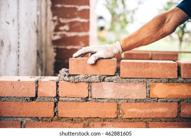 industrial bricklayer worker placing bricks on cement while building exterior walls, industry details