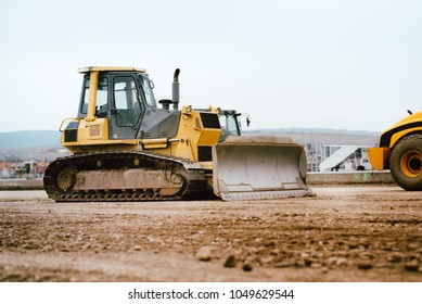 industrial building construction site mini bulldozer levelling and moving soil during highway building