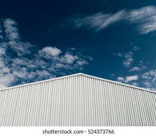 Industrial building with corrugated sheet metal facade forming an up arrow, progress, success concept