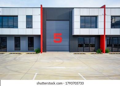 Industriegebäude mit leerem Parkplatz. Geschlossene Lagertür mit einer großen Zahl von 5 gestrichen.