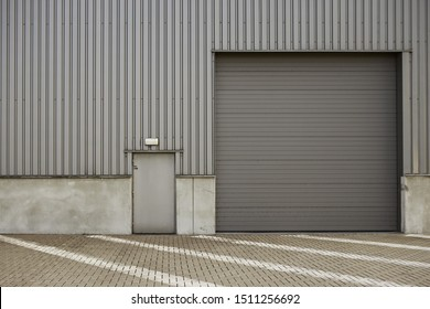 Industrial building made of metal corrugated board with roll-down shutter and locked door with private access for personnel, white marking on red paved stone surface. Urban and construction concept