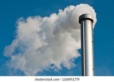 Industrial building with one high grey chimney background on blue sky