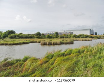 Industrial buildings overlooking a river and nature reserve.