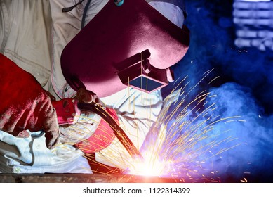 Industrial business with metal welding wear equipment protective for safe by Mig machine during process at construction site on dark tone background