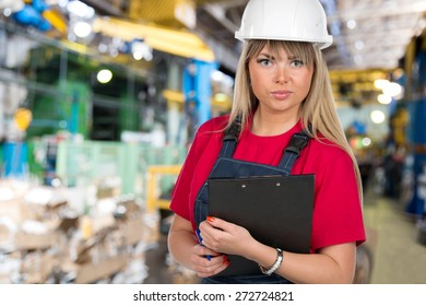 Industrial caucasian female inspector worker with clipboard at factory workshop background