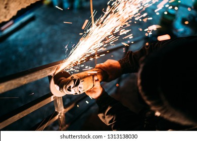 industrial caucasian male worker, close up workers hands with power tool with circular blade grinder