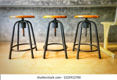 industrial chair set, wooden base and steel stand, base height adjustment by spinning. dark gray cement as background. blur at picture edge.