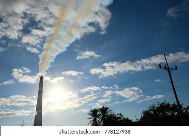 Industrial chimney over blue sky