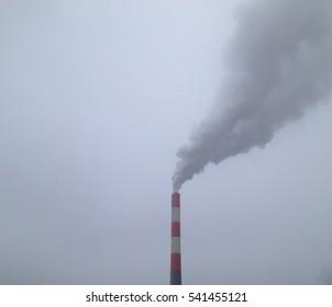 Industrial chimney smoking in the grey dark sky