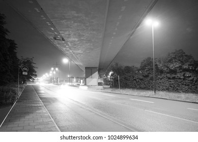 Industrial city part with concrete bridge on rainy night