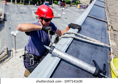 Industrial climber, alpinist, is passes over roof edge. He is climb down to applying silicone to rubber juncture among building glass facade.