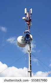 Industrial climber in dirty blue cloth install,  tune, antenna at big height. Blue sky at the background of a labor man.