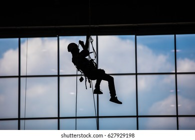 Industrial climber hangs from ropes inside industrial building