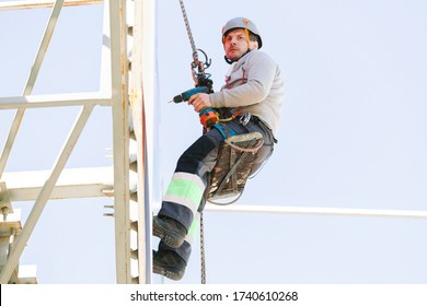 Industrial climber in helmet and overall working on height. Risky job. Professional worker