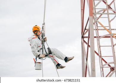 Industrial climber in helmet and uniform paints metal construction with paint roller. Professional Painter working on height. Risky job. Extreme occupation.