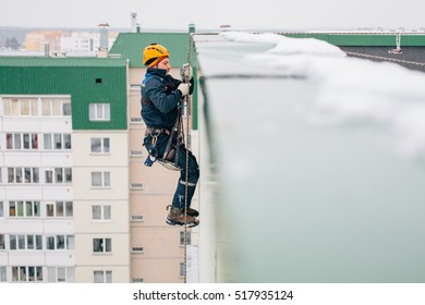 Industrial climber in uniform and helmet rises to the snowy roof in winter.