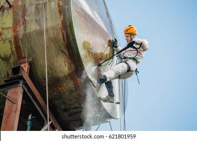 Industrial climber washing big barrel with water pressure. Risky job.