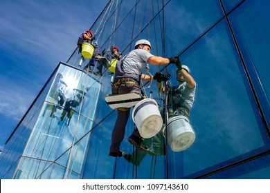 Industrial climbers are applying silicone to rubber juncture among building's glass facade.