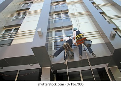 Industrial Climbers Washing Facade of a Modern Building. Window and Facade Cleaning. Glass Cleaning Services.