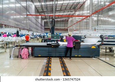 Industrial cloth cutting machine and fabric cutting area in garment factory in industrial zone in Ho Chi Minh City, Vietnam, with modern machinery and technology systems.